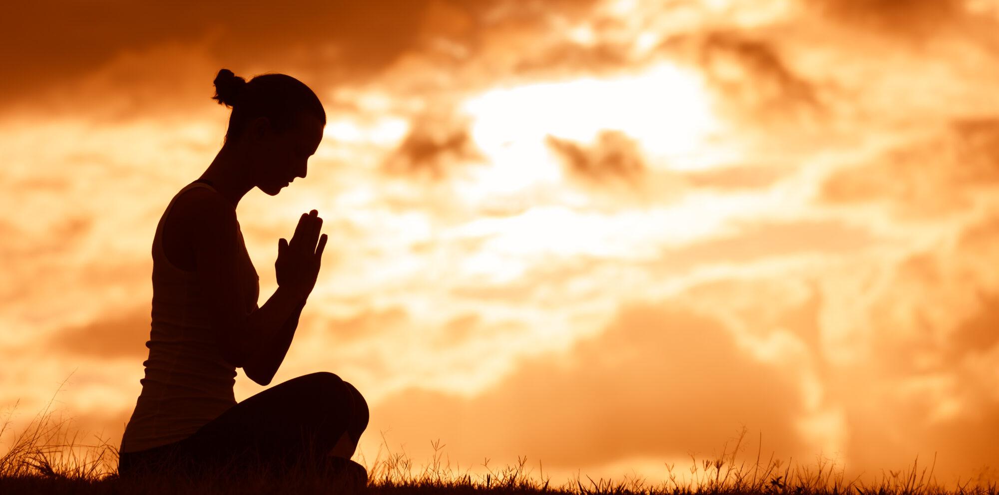 Silhouette of woman praying.