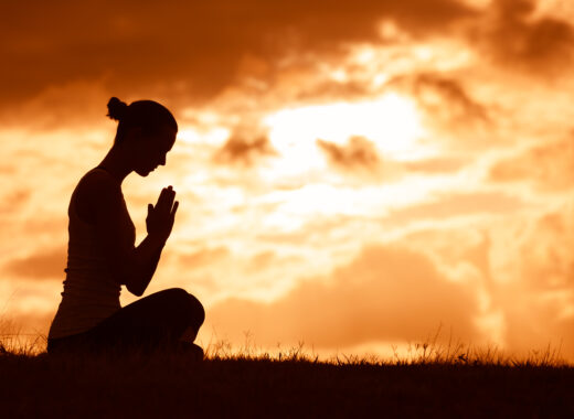 Silhouette of woman praying.