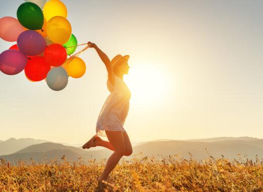 Female running through desert trailing a dozen balloons