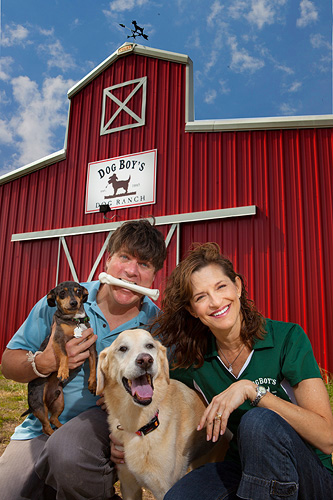 dog trainers in front of red barn