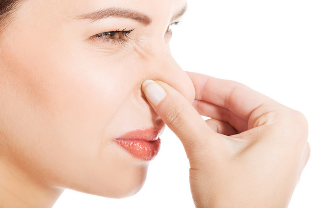Blog image illustrating smells: Woman holding nose