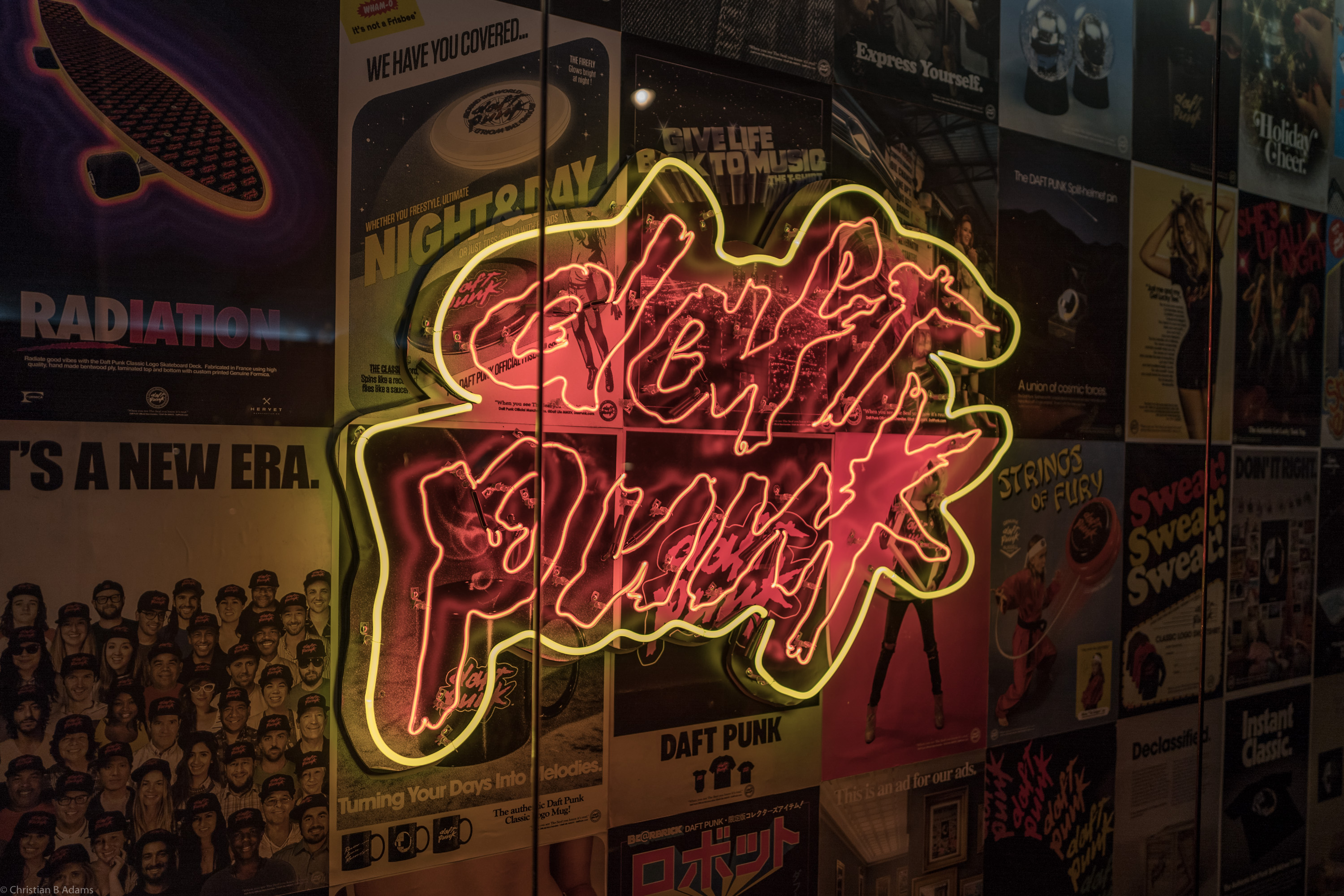 A neon Daft Punk Logo is flanked by posters featuring licensed Daft Punk Merchandise at the Daft Punk Pop Up at Maxfield Gallery in Los Angeles in February of 2017.