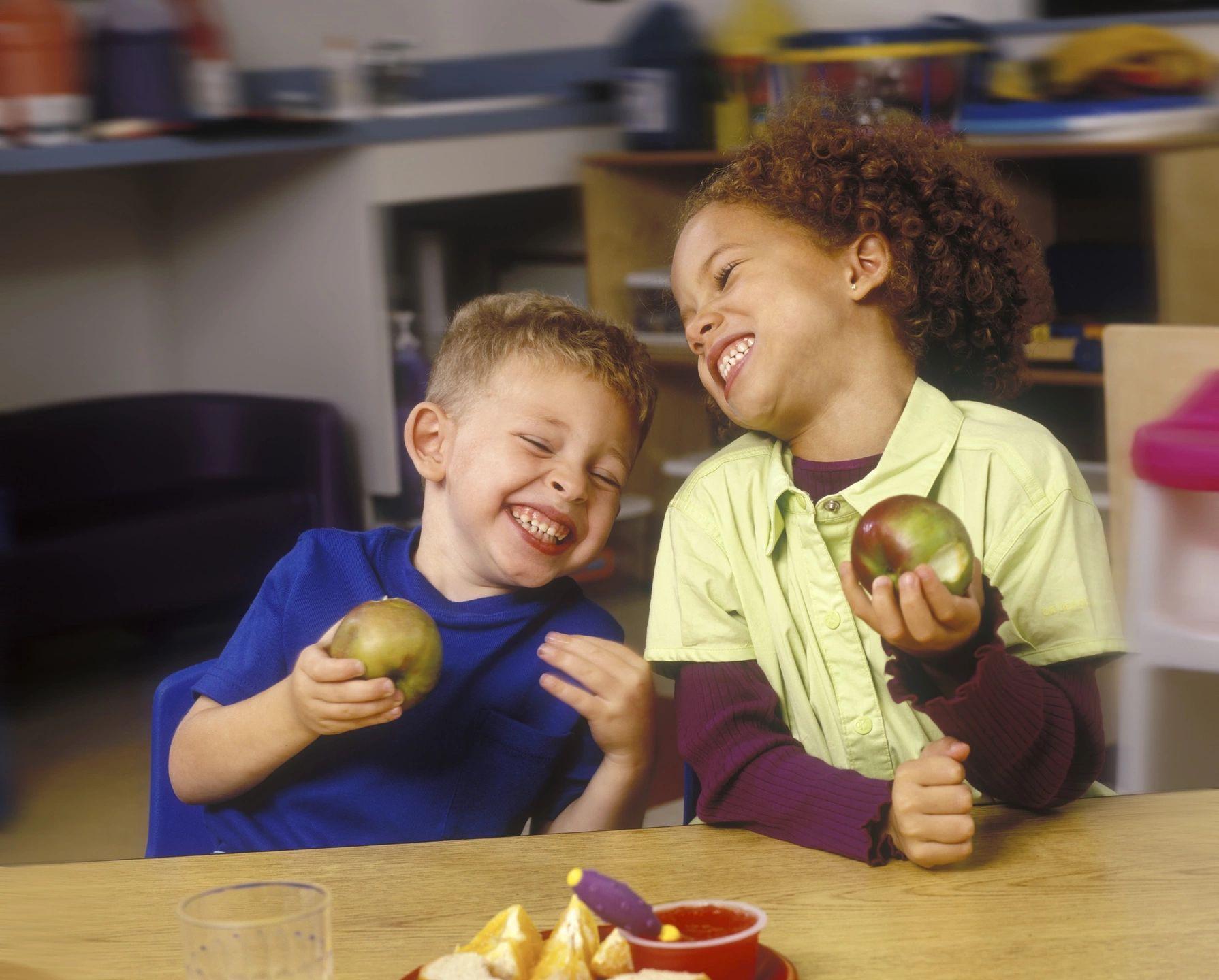 Two children eating fruit