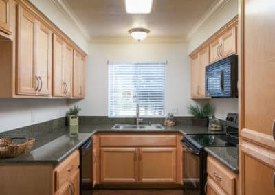 Kitchen with granite countertops, maple cabinets, and black appliances