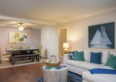 White couch with blue and green pillows in the Living area and long table with chairs and bench in the dining area