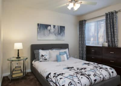 Master Bedroom with bedside table, lampshade, ceiling fan, and window with blinds