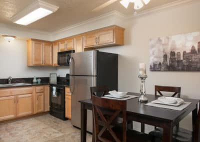 Kitchen with dining table, cabinets, and black countertops