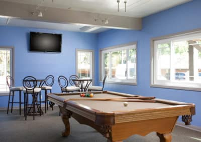Billiards table in a game room with blue walls and windows