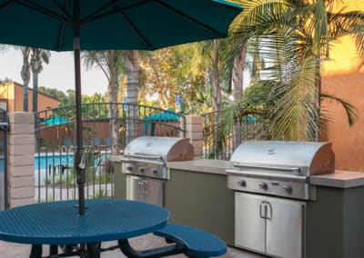 Blue picnic table with umbrella by two BBQ grills near the pool area
