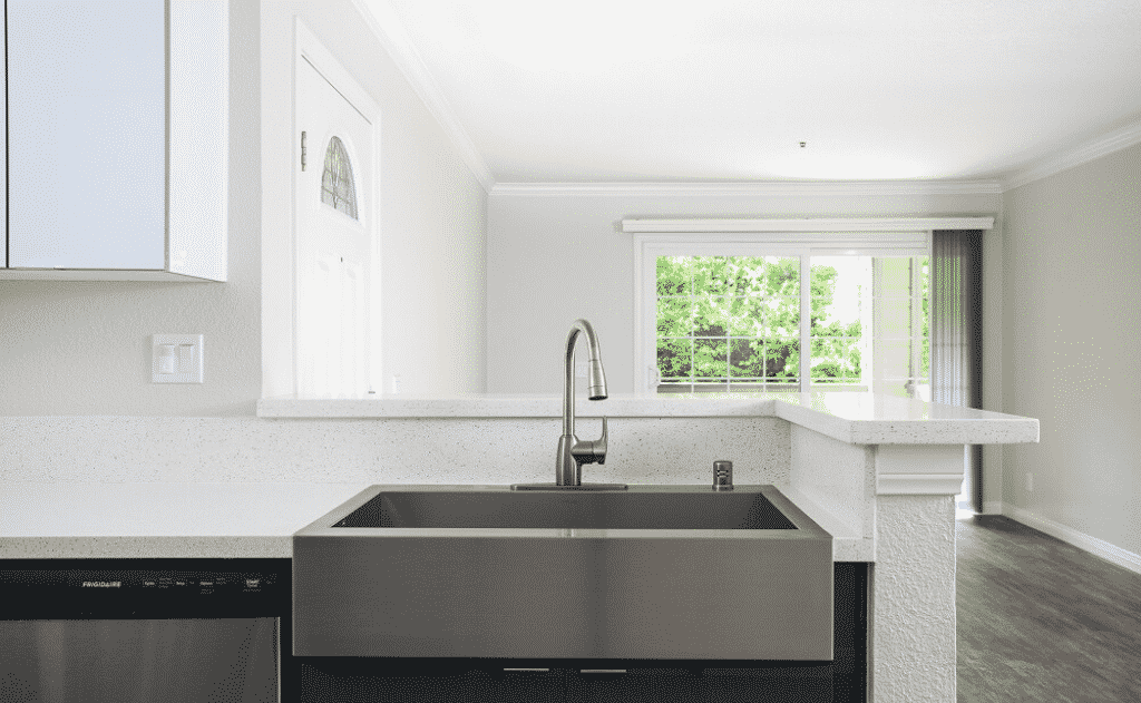 Kitchen sink and view of living room with balcony