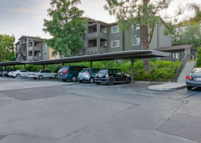 Covered parking area with cars and trees