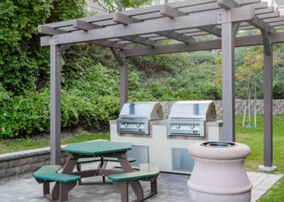 Picnic area with two BBQ grills, picnic table, and grass