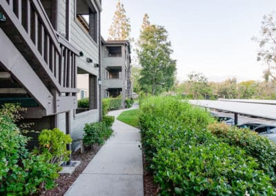 landscaped pathways along the parking and exterior of apartment building