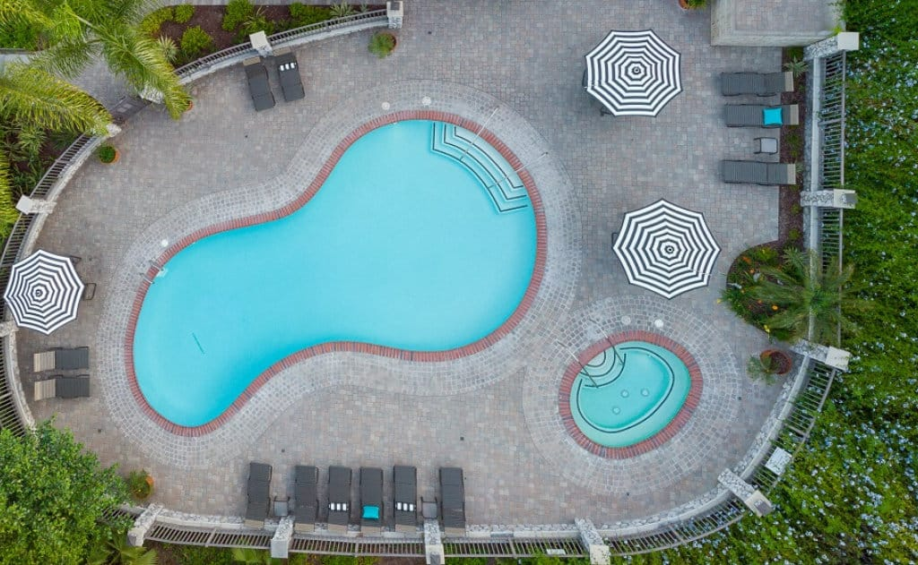 Drone view of the pool, spa, three striped umbrellas, and pool furniture