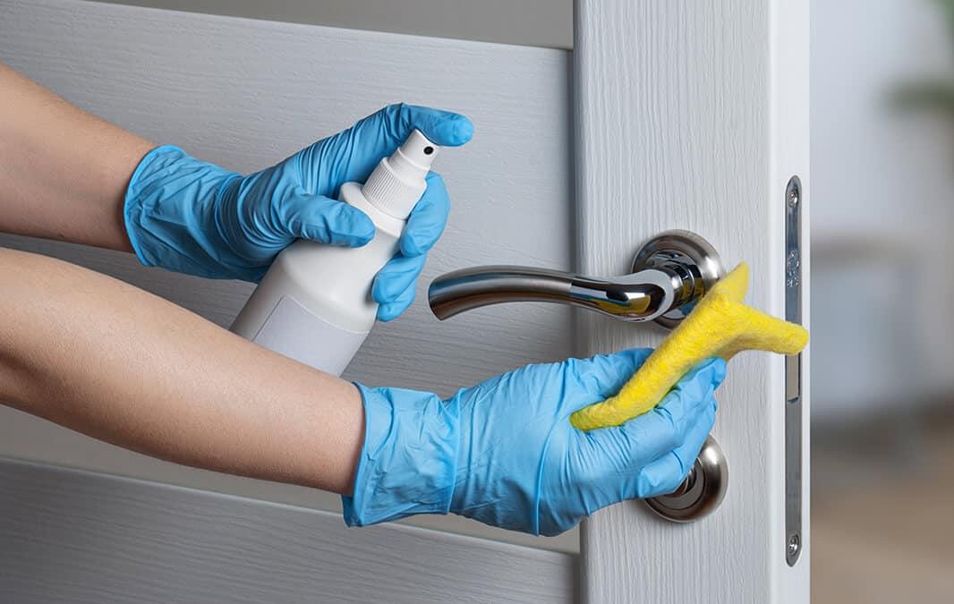 hand spraying the door handle