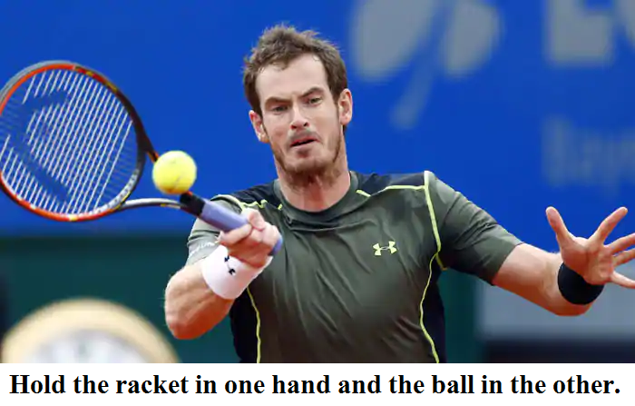 Hold the racket in one hand and the ball in the other.