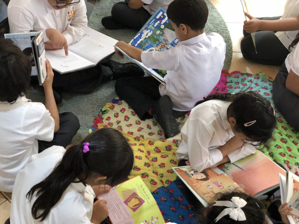 Children browsing books during a school visit to Maktaba.