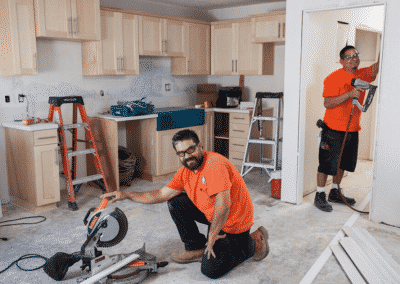 two construction workers holding power tools and building kitchen