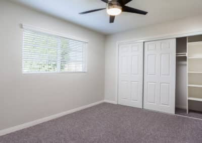Bedroom with ceiling fan, carpet, and large closet
