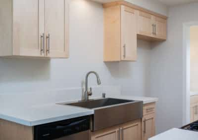 Stainless steel farmhouse sink and appliances with quartz counters and maple cabinets in the kitchen