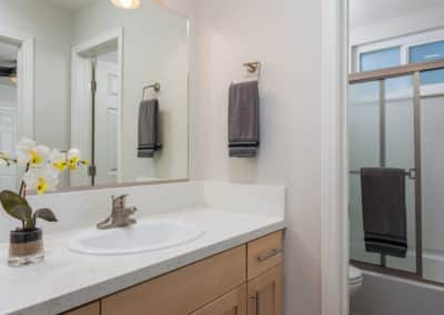 Quartz counters and maple cabinets in the bathroom