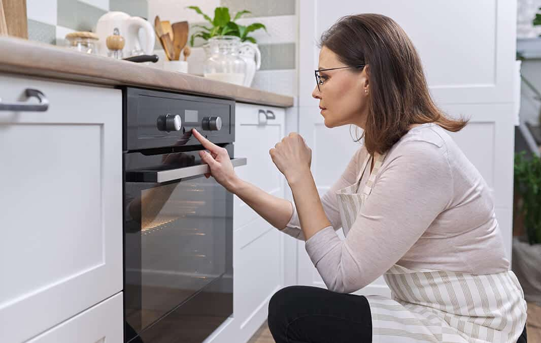 woman looking at oven