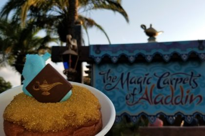 "The ""Wish Granted Donut"" in front of ""The Magic Carpets of Aladdin"" ride sign at Walt Disney World."