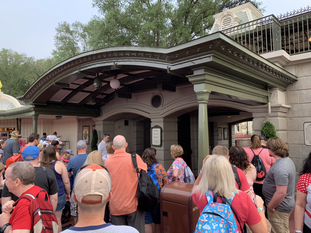 Adults and a few children lined up waiting to get into Magic Kingdom in Walt Disney World.