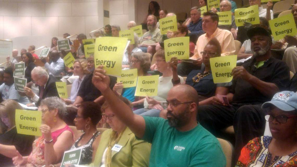 Charlotte citizens hold Green Energy signs