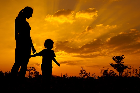 silhouette of a mother and son who play outdoors at sunset background