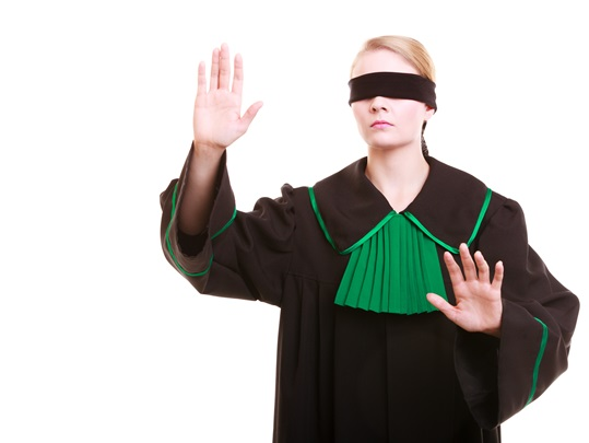 Lawyer attorney in classic polish gown covering eyes with blindfold