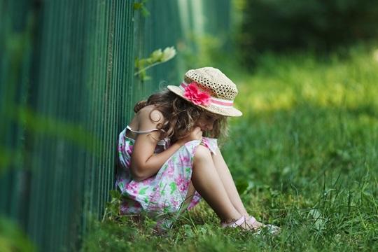 Sad little girl sitting on grass