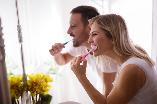 man and woman brushing their teeth