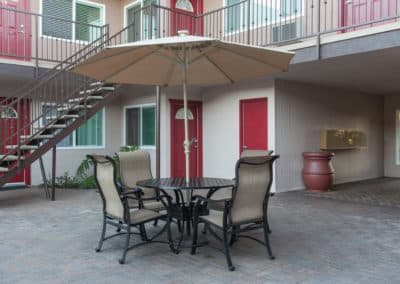 picnic table and chairs with umbrella along outdoor stairs