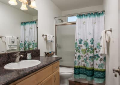 Bathroom with flower curtain, sink, toilet, and wide mirror