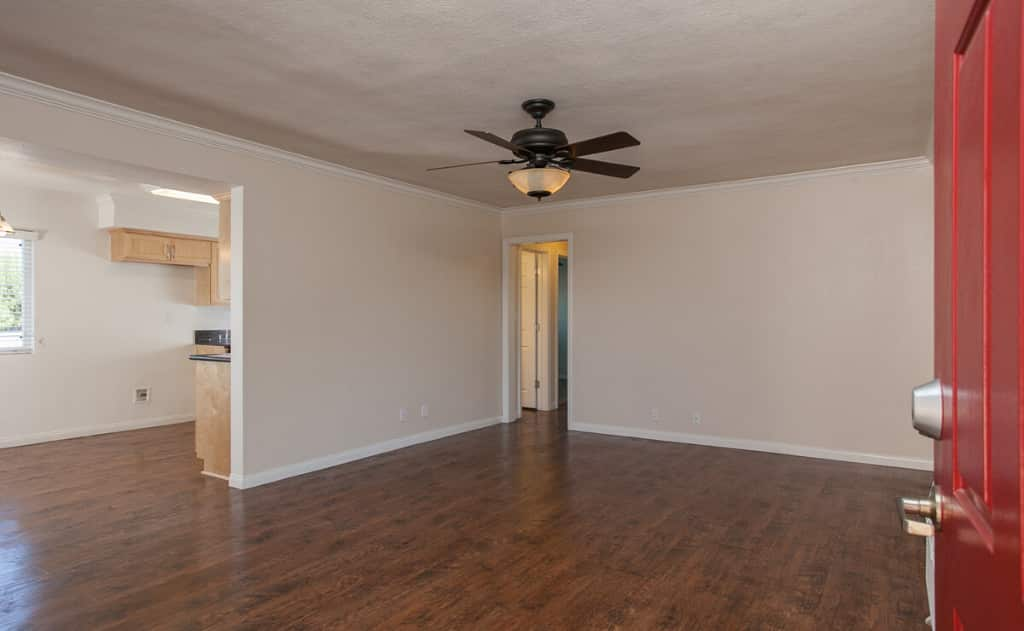 Red door opening to living room with wood flooring