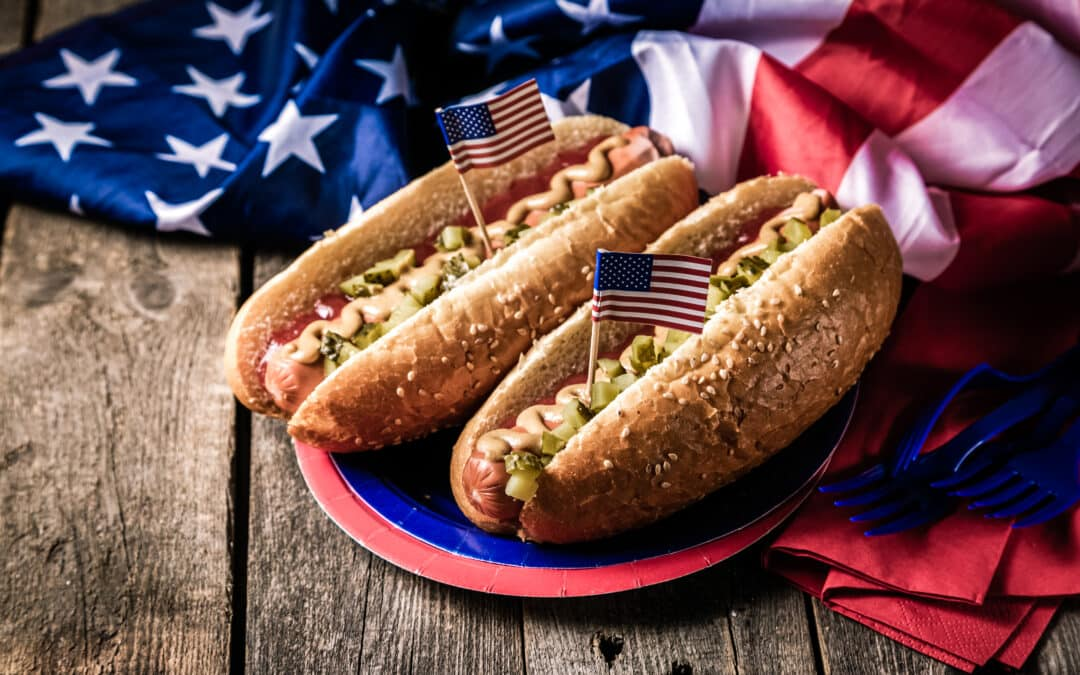 2 hotdog sandwich on a plate beside the american flag