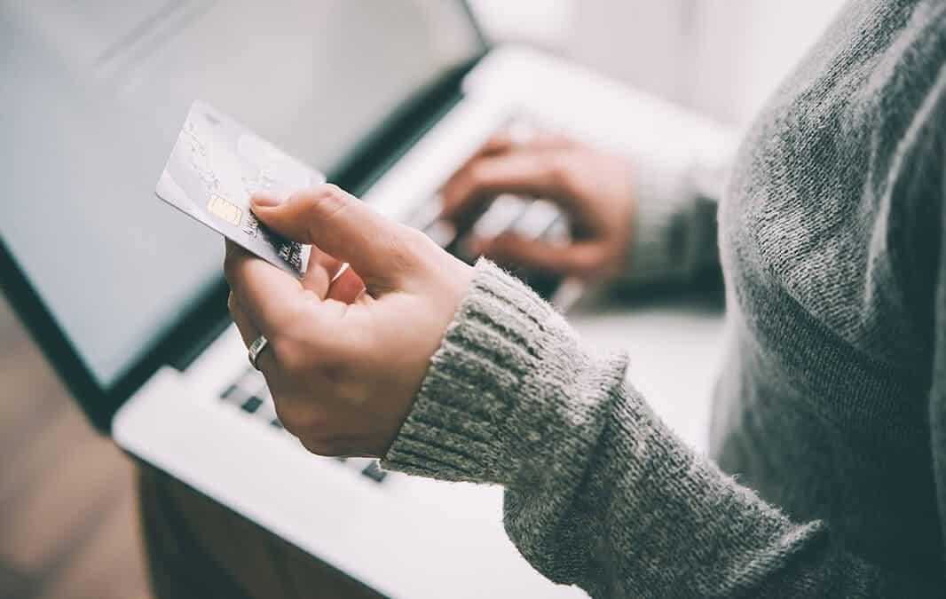 Person using credit card at computer