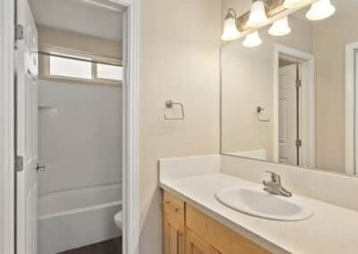 Granite counter and sink and door open to toilet and shower/bathtub