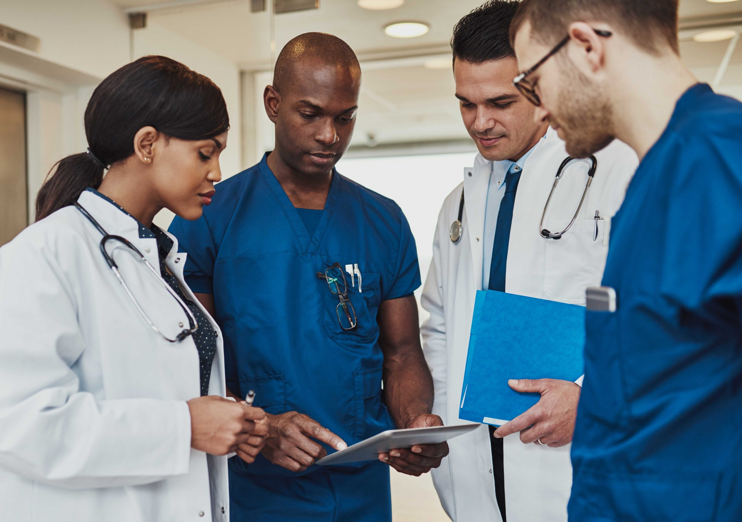 Multiracial team of doctors discussing a patient standing grouped in the foyer looking at a tablet computer, close up view