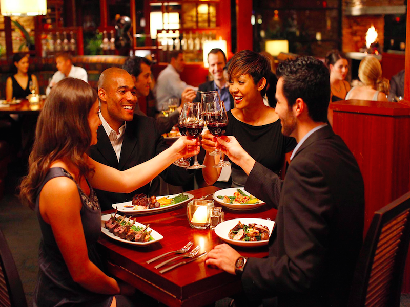 Two couples enjoying a meal at a nice bistro