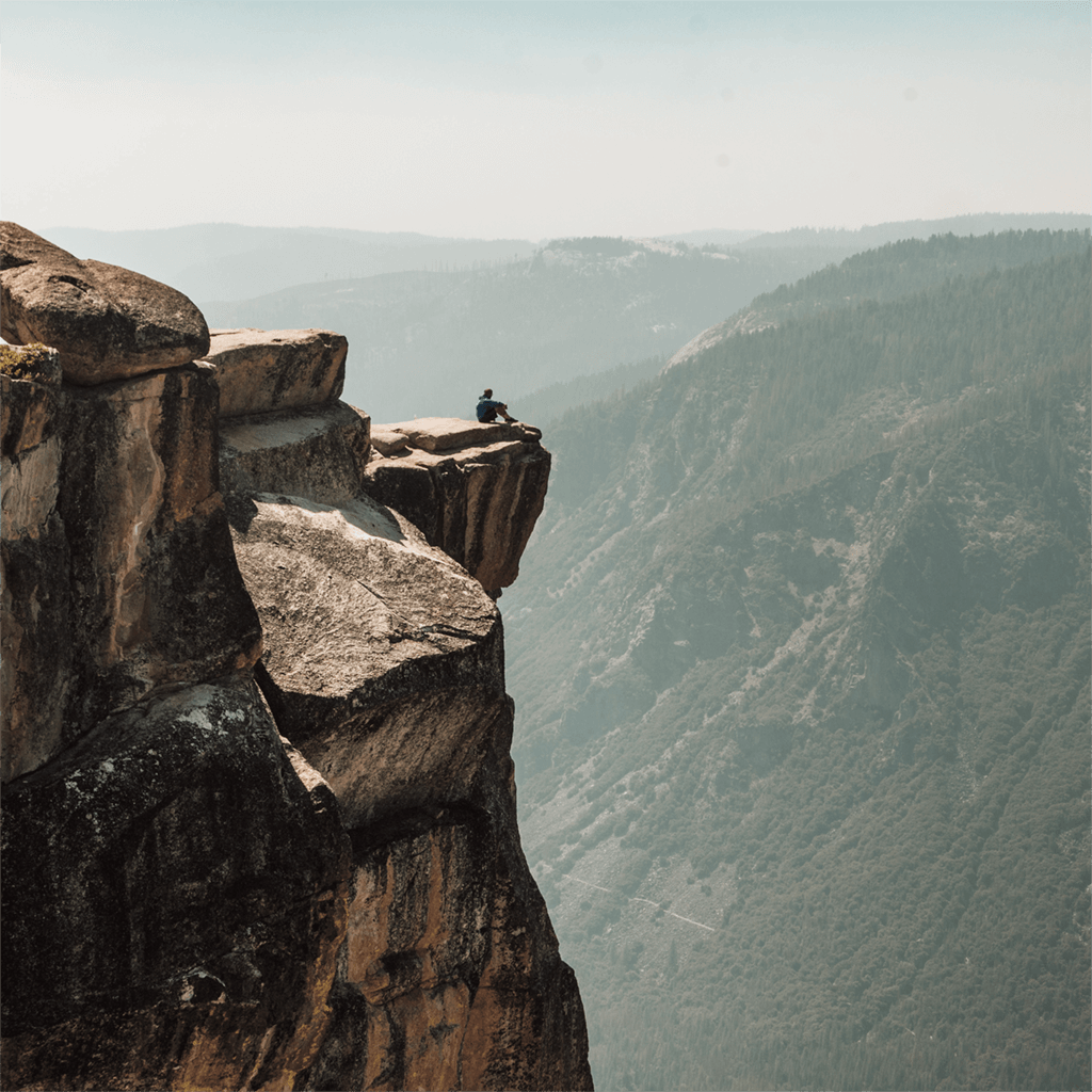 man sitting on edge of cliff