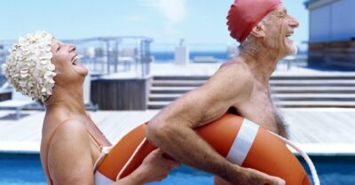 Side view of senior couple poolSide laughing and holding a lifebuoy