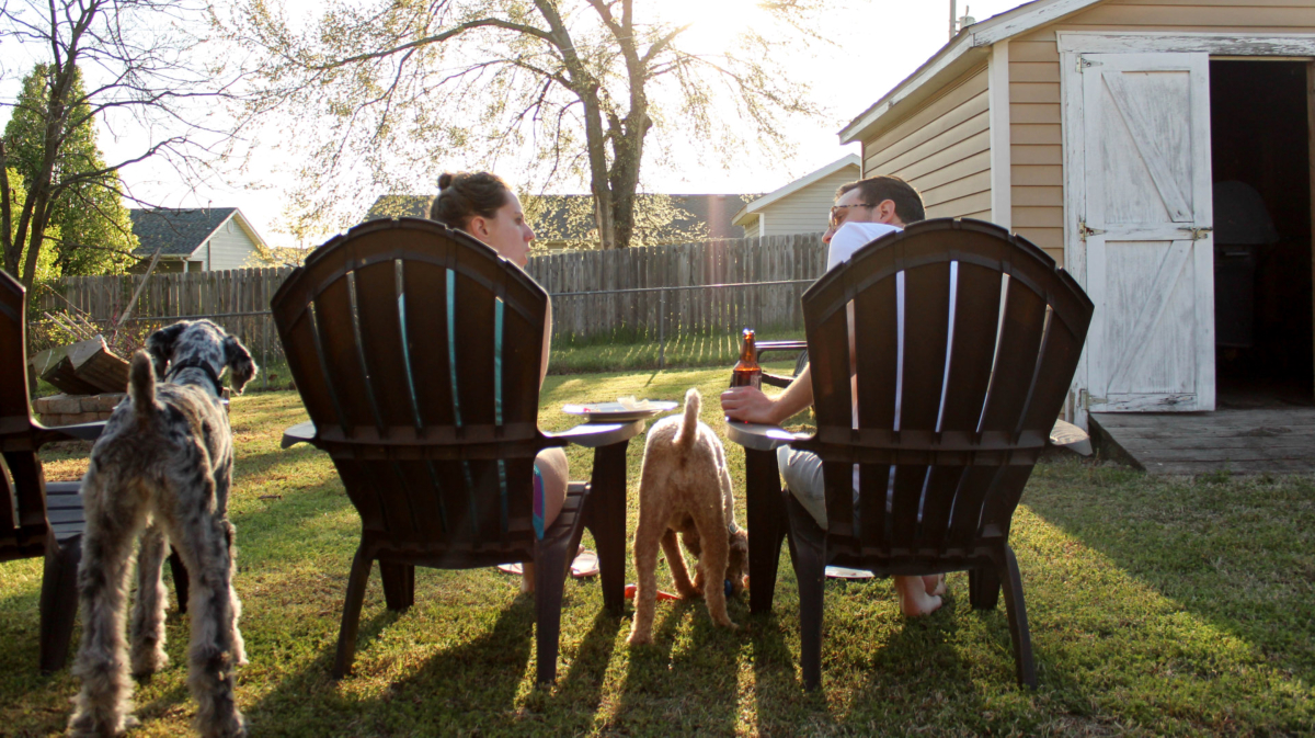 A couple and their dogs enjoying the back yard. Photo by KaLisa Veer on Unsplash.