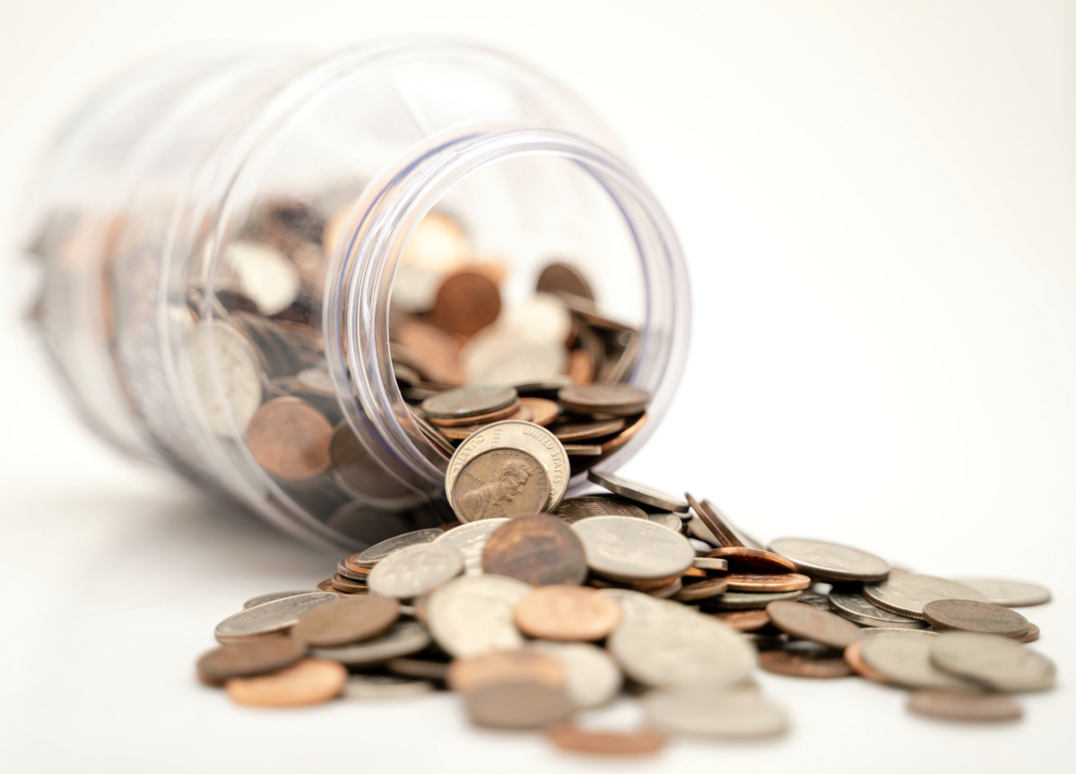 Coins spill from a jar. Photo by Michael Longmire on Unsplash
