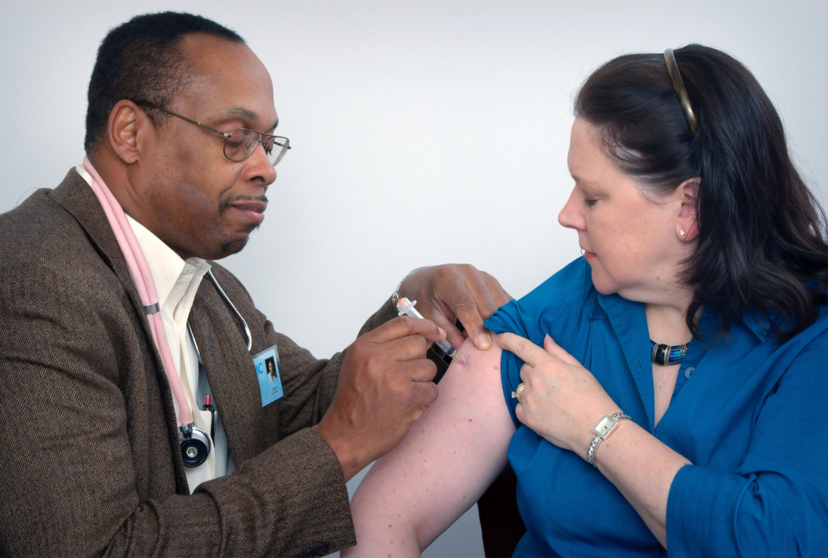 A doctor gives an immunization to a patient. Photo by CDC on Unsplash.
