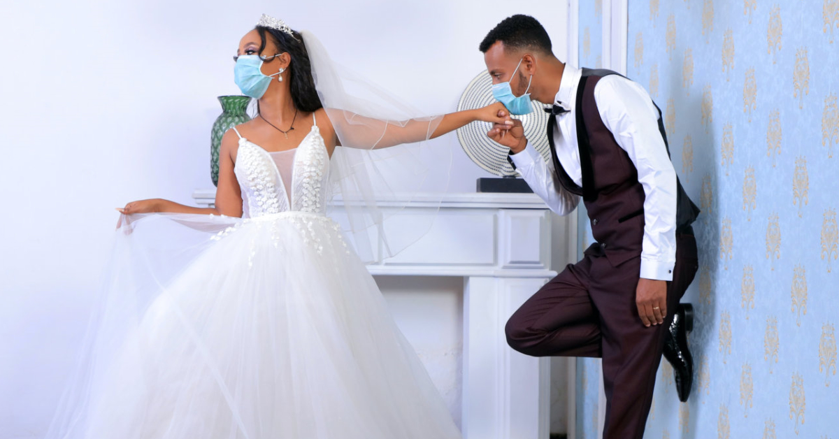 A bride and groom wearing surgical masks. Photo by mulugeta wolde on Unsplash.