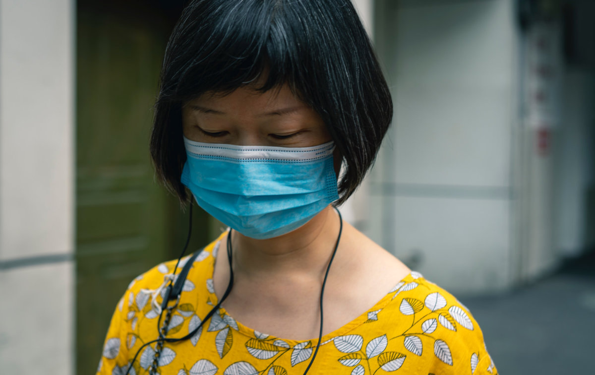 A woman wearing a face mask to reduce transmission of COVID-19. Photo by Li Lin on Unsplash.