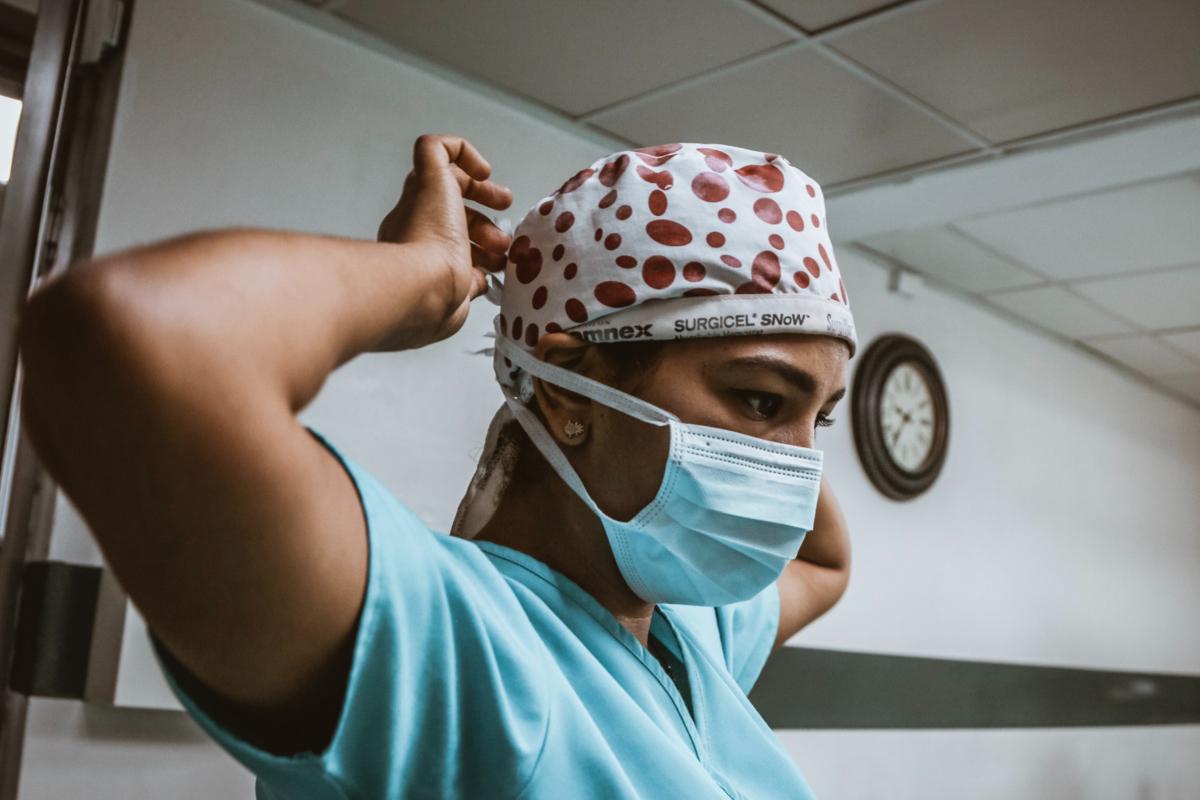 A woman wearing scrubs and a mask. Photo by SJ Objio on Unsplash