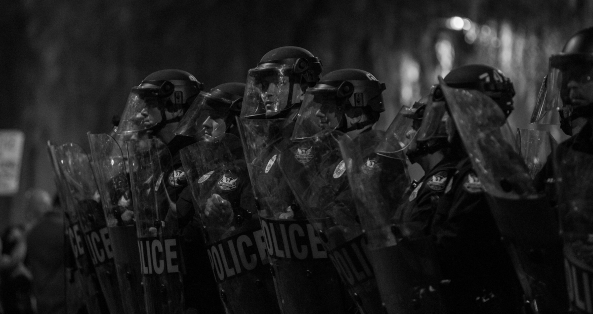 Police with riot control shields and helmets. Photo by Slaven Gujic on Unsplash